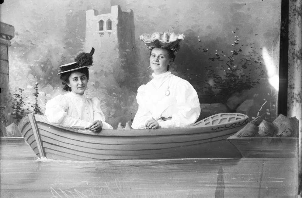 Two women seated in a prop boat with an artistic back drop, via the Albert J. Ewing Collection.