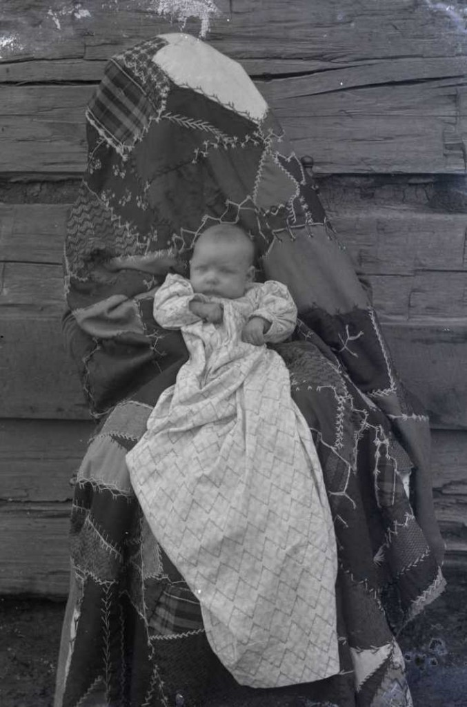 "A ""hidden mother"" beneath a quilt in another of Ewing's photographs, via Ohio Memory."