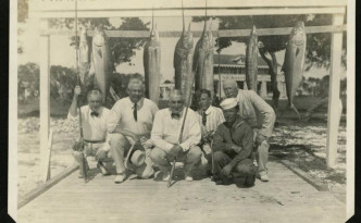 Harding poses with a group of fishermen with their day's catch in St. Augustine. Via Ohio Memory.