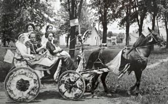 The Munn sisters of Portage, Ohio, in a decorated horse-drawn surrey for their local 4th of July parade. Courtesy of the Wood County District Public Library on Ohio Memory.