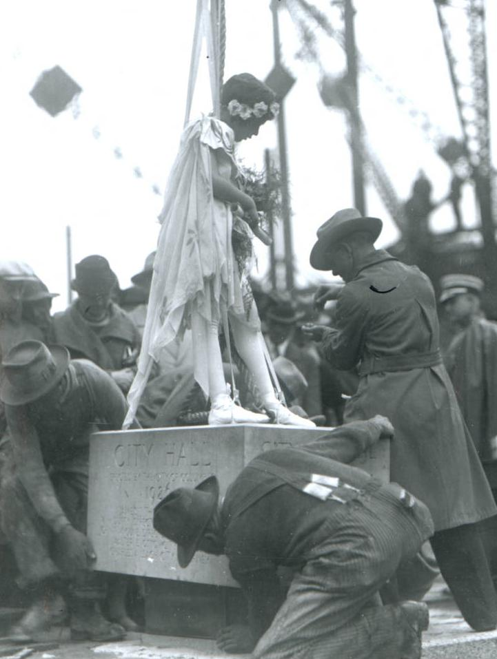 A young girl dressed as Miss Liberty rides the cornerstone for City Hall in Columbus in 1962. Via Ohio Memory.