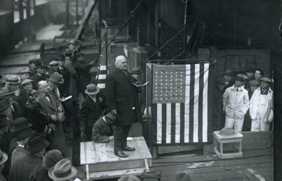 Founder of the American Insurance Union John J. Lentz delivers a speech at the cornerstone laying ceremony of the AIU Citadel building. The cornerstone sits to his left, hidden behind the American flag. Via Ohio Memory.