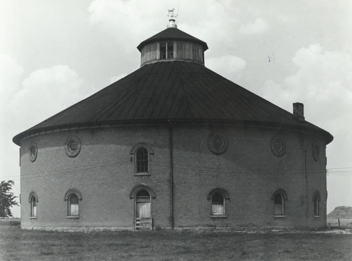 This round brick barn in Urbana is part of a former farm known as Nutwood Place. The barn, built in 1861, has a cupola with a horse weathervane on top. Nutwood Place is listed on the National Register of Historic Places.