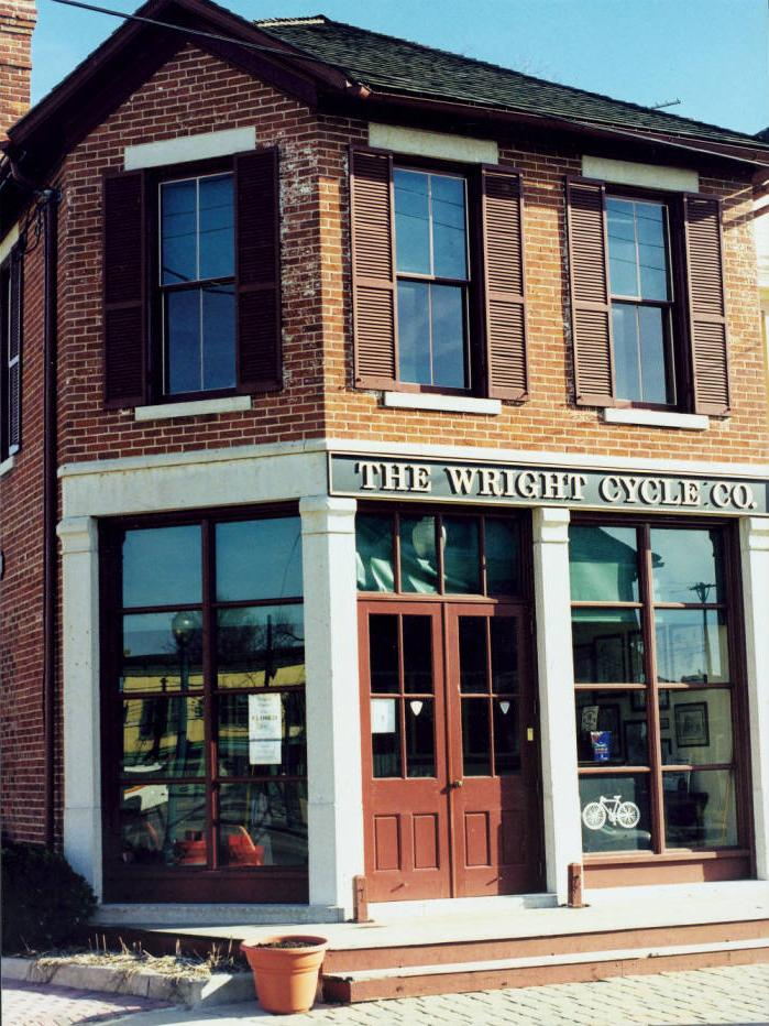 Before Orville and Wilbur Wright began working on solving the problem of flight, they ran a newspaper and a bicycle shop. This is the fourth of five locations of the Wright Cycle Company in Dayton. Wilbur and Orville occupied the building, located at 22 South Williams Street, from the spring of 1895 to the fall of 1897. The building represents the first time the Wrights' printing and bicycle businesses were together under the same roof. The Wright brothers began their business repairing bicycles in 1893. By 1896 they were manufacturing their own Van Cleve and St. Clair bicycles. While working at the bicycle shop, Wilbur read of the death of a German glider pilot and became interested in flying. After extensive research and testing, the Wright brothers became the first to fly a heavier-than-air craft on December 17, 1903. The Wright Cycle Shop is the center of the neighborhood in which the Wright Brothers lived and worked, and it is the only one of the Wright brothers' bicycle shops that remains intact on its original location. It was designated a national historical landmark in 1992 as one unit of Dayton Aviation Heritage National Historical Park. The building is listed on the National Register of Historic Places. Courtesy of the Dayton Aviation Heritage National Historical Park via Ohio Memory.
